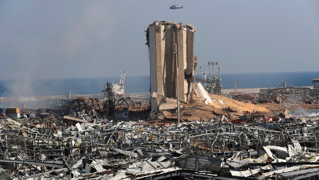 A Lebanese army helicopter flies over the scene where an explosion hit the seaport of Beirut, Lebanon. AP