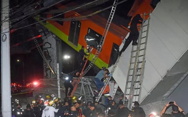 Bombeiros e equipes de resgate trabalham para retirar vítimas de vagão que caiu depois que um trecho da Linha 12 do metrô desabou na Cidade do México — Foto: Jose Ruiz/AP