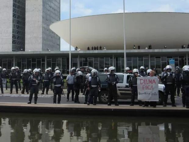 Junto a barreira de policiais, manifestante pró-Dilma exibe cartaz em frente ao Congresso Nacional  (Foto: Vianey Bentes/TV Globo)