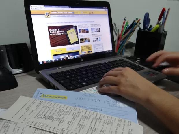 Professora mostra página da instituição bancária que foi clonada por fraudadores (Foto: Waldson Costa/ G1)