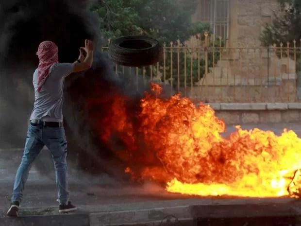 Jovem coloca fogo em pneu durante protesto depois do enterro de menino de 13 anos morto em campo de reugiados em Belém (Foto: AFP PHOTO / MUSA AL-SHAER)