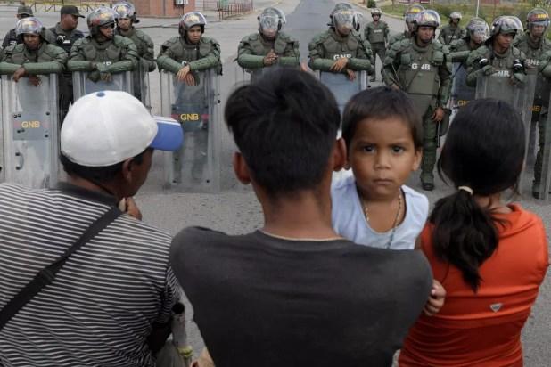 Na expectativa de cruzar a fronteira, pessoas aguardam diante de paredão de soldados venezuelanos em Pacaraima (RR) — Foto: Ricardo Moraes/Reuters