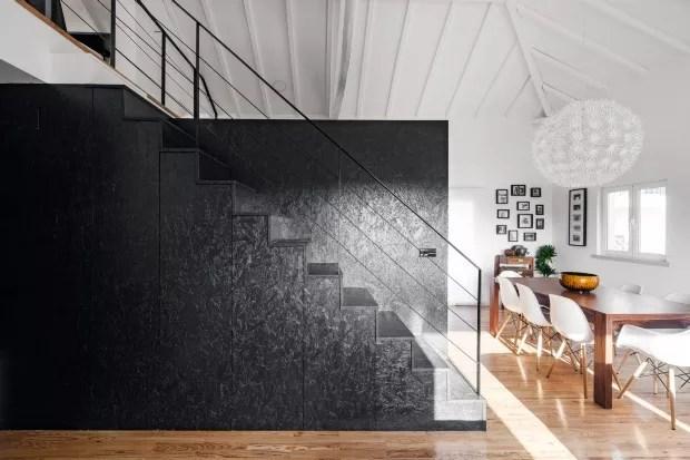 Pintado de preto, o OSB trouxe uma atmosfera contemporânea à área. O volume serve como suporte para a escada e armários (Foto: João Morgado / Divulgação)
