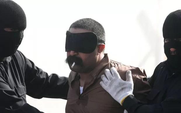 Saudita condenado à morte fuma um cigarro antes de sua execução no Kuwait (Foto: Yasser Al-Zayyat/AFP)