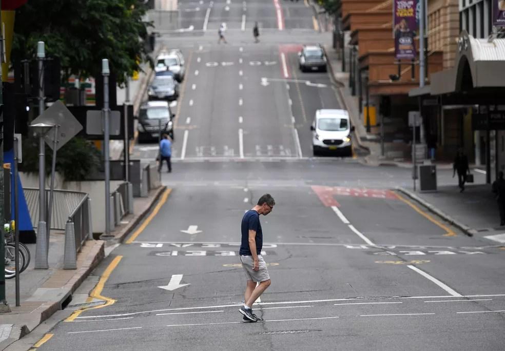 Homem caminha em rua vazia de Brisbane, na Austrália, em 30 de março, após imposição de lockdown na cidade — Foto: AAP Image/Darren England via Reuters