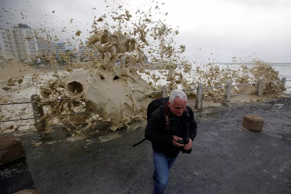 7 de junho - Um homem corre de uma onda após tempestades atingirem o mar da Cidade do Cabo, na África do Sul (Foto: Mike Hutchings/Reuters)