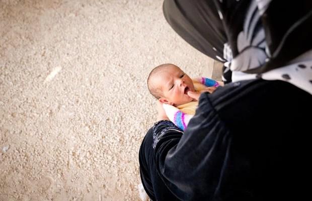 Mãe aguarda com bebê fora da tenda para ser registrado em campo na Jordânia (Foto: J. Kohler/Unhcr)
