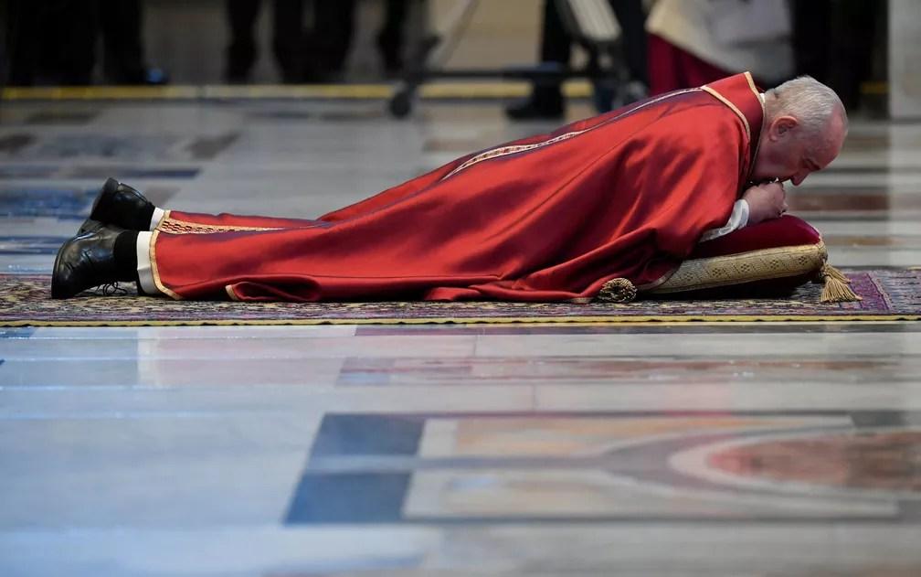 Papa Francisco se deita no chão da basílica de São Pedro, no Vaticano, em sinal de humilde obediência durante missa da Sexta-Feira Santa, no dia 10 de abril — Foto: Vatican Media/Handout via Reuters