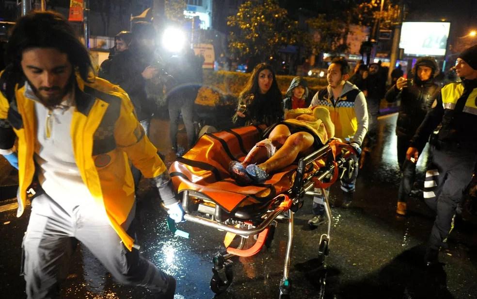 Mulher ferida é retirada por paramédicos do clube Reina, em Istambul, após ataque durante comemoração do Ano Novo (Foto: Murat Ergin/Ihlas News Agency via Reuters)