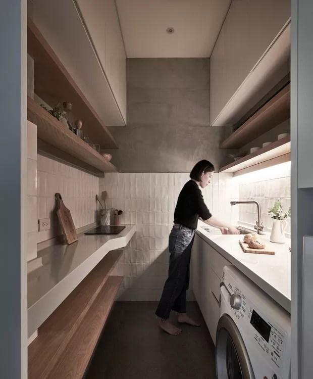 Um corredor dá lugar à cozinha e as prateleiras de madeira economizam espaço. Armários superiores servem para guardar objetos menos utilizados (Foto: Hey! Cheese/ Dezeen/ Reprodução)