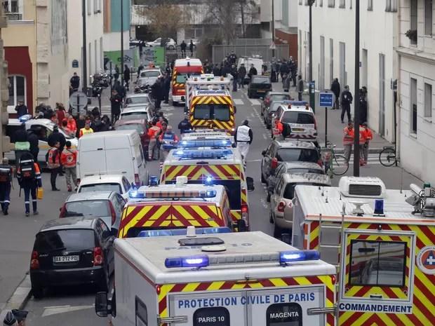 Rua da sede da revista 'Charlie Hebdo' é tomada por ambulâncias após o atentado a tiros à publicação satírica que eventualmente fazia piadas com o profeta Maomé (Foto: François Mori/AP)