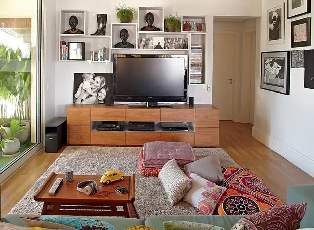 Da sala de TV enxerga-se a composição de vasos na varanda. O rack é de freijó com pintura laqueada e é desenho da arquiteta Bruna Riscali, que também assina o projeto. Almofadas, futons e tapete imprimem conforto ao ambiente (Foto: Victor Affaro/Editora Globo)
