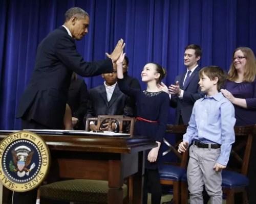 O presidente dos EUA, Barack Obama, dá um 'high five' em menina que escreveu a ele pedindo mais controle de armas nos EUA, nesta quarta-feira (16), durante ato na Casa Branca (Foto: Reuters)