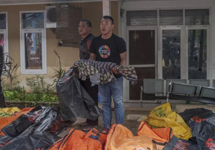 Homem segura corpo de criança vítima de tsunami, que atingiu a praia de Carita, na Indonésia, na noite deste sábado (22) — Foto: AP Photo/Fauzy Chaniago