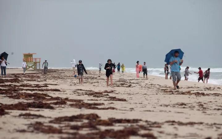 Pessoas caminham pela praia em Miami Beach, nos EUA, antes da chegada do furacão Matthew