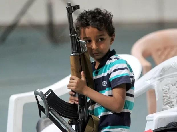 Crianças comemoravam com rifle nas mãos (Foto: Mohamed al-Sayaghi/Reuters)