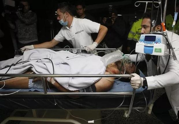 Médicos e enfermeiros da Clínica San Juan de Dios transportam o jogador brasileiro Alan Ruschel, um dos sobreviventes do acidente com o avião que transportava o time do Chapecoense na Colômbia (Foto: Luis Eduardo Noriega A./EFE)
