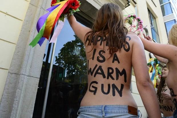 Ativistas com inscrição 'a felicidade é uma arma quente' protesta nesta quinta-feira (29) em Berlim (Foto: John MacDougall/AFP)