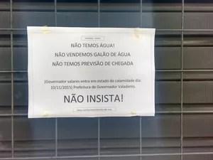 Este cartaz foi pregado na porta de uma distribuidora de água (Foto: Diego Souza/G1)
