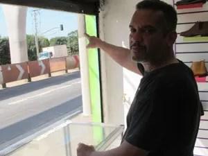 Sapateiro Joseílton de Moura trabalha em frente à obra do monotrilho; ele aponta para coluna onde desconhecidos colocaram duas bananas de dinamite e fio para acionar pólvora (Foto: Kleber Tomaz / G1)