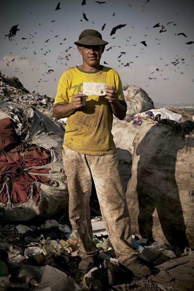 """""""APRENDER A ADMINISTRAR"""" - Denilson Ferreira de Souza, 44 anos, trabalha como carpinteiro com carteira assinada há quatro meses. Está se adaptando à nova vida: ganhos diários menores em termos financeiros, mas com mais estabilidade e direitos trabalhistas. Não sabe precisar quanto tempo passou em Gericinó, mas se lembra bem de quanto o lixão rendia em suas contas. """"Tiro de R$ 300 a R$ 400 por dia"""", disse ele quando foi fotografado com uma das cartas que catou lá. """"Hoje tenho que planejar para passar o mês."""" (Foto: Micha Ende)"""