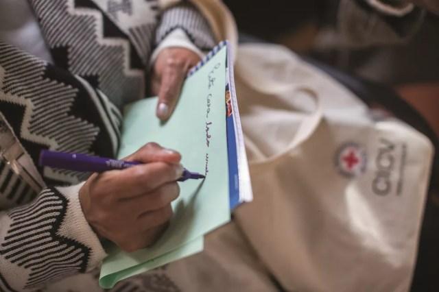 Familiar de pessoa desaparecida escreve em um papel durante reunião do Comitê Internacional da Cruz Vermelha (CICV) em São Paulo — Foto: Victor Moriyama/CICV
