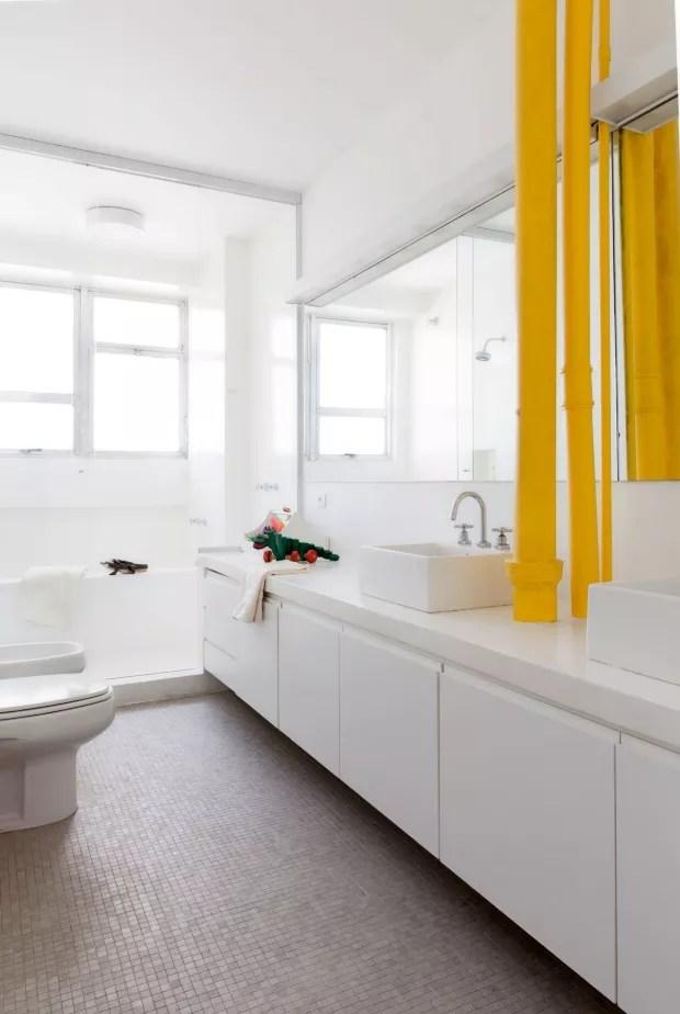 Banheiro das crianças. Um gabinete todo de madeira pintado de epóxi branco acopla as duas pias da Deca, entre as quais há um encanamento exposto, tingido de amarelo. O piso é de pastilhas Jatobá, e a iluminação, da Reka (Foto: Maíra Acayaba / Editora Globo)