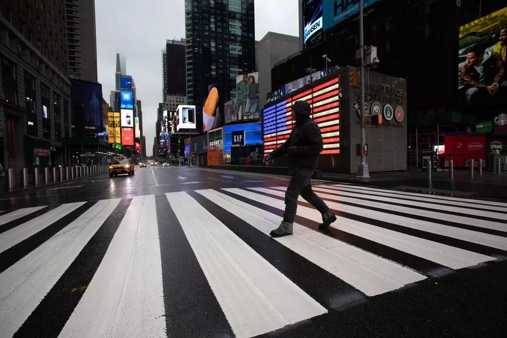 NOVA YORK - Um homem atravessa a rua em uma Times Square quase vazia na manhã desta segunda-feira (23) em Nova York. O governador Andrew Cuomo ordenou que a maioria dos nova-iorquinos ficasse em casa para diminuir a pandemia de coronavírus — Foto: Mark Lennihan/AP
