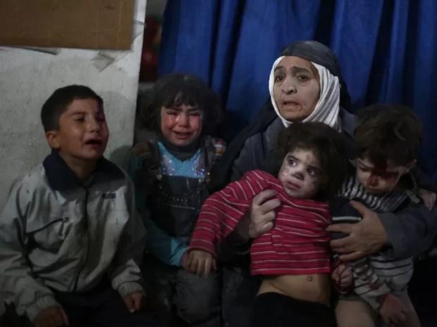 Uma mulher acompanha crianças que aguardam atendimento em uma clínica improvisada na região de Douma, na Síria, após ataques aéreos das forças do governo, no domingo (15) (Foto: AFP Photo/Abd Doumany)