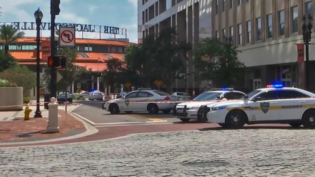 Carros da polícia bloqueiam uma rua que conduz à área de Jacksonville Landing, no centro de Jacksonville, na Flórida (Foto: HO/Courtesy of WJXT/AFP)