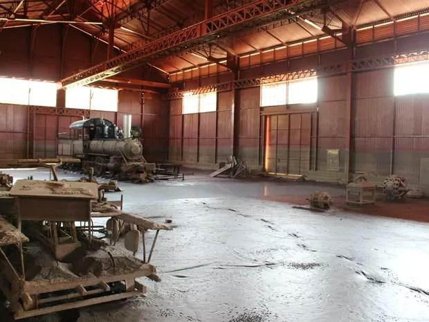Galpão do Museu Histórico da Estrada de Ferro Madeira Mamoré coberto por terra da cheia do Rio Madeira (Foto: Gaia Quiquiô/G1)