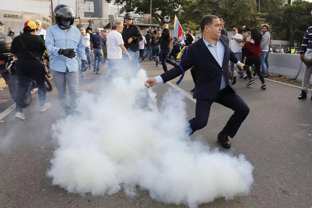 Homem contrário ao governo de Nicolás Maduro atira de volta uma bomba de gás lacrimogêneo atirada por militares da base aérea 'La Carlota', diante da qual um grupo se concentra em Caracas — Foto: Ariana Cubillos/AP