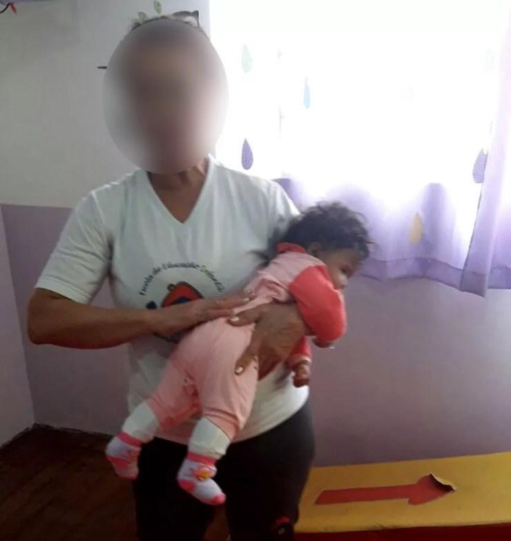 Foto enviada pela escola mostra funcionária da creche em Campinas colocando bebê para dormir (Foto: Devair Maciel / Arquivo pessoal)