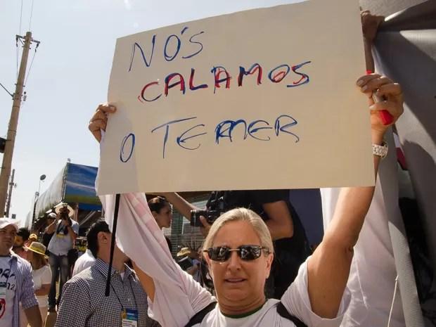 Manifestante mostra cartaz após o vice-presidente da República Michel Temer cancelar discurso na Agrishow (Foto: Érico Andrade/G1)