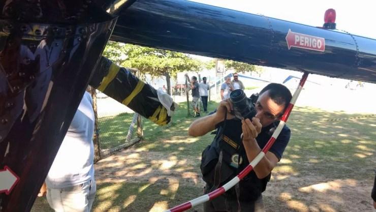Perito fotografa helicóptero para analisar marcas que podem ser de tiro (Foto: Marcos Serra Lima/G1)