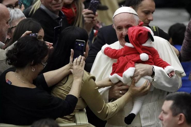 Papa Francisco carrega uma das crianças no domingo (16). — Foto: AP Photo/Gregorio Borgia