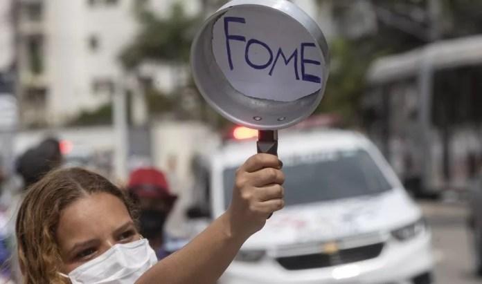 Moradora de Paraisópolis mostra panela vazia durante protesto em São Paulo na segunda-feira (5) — Foto: André Penner/AP Photo
