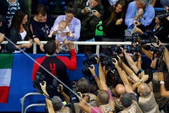 Phelps vai até esposa, mãe e filho após receber medalha (Foto: Reuters)
