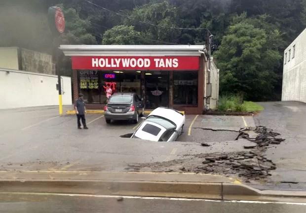 Carro foi engolido por cratera que se abriu em estacionamento de estrada (Foto: Roxanne Oglesby/Reuters)
