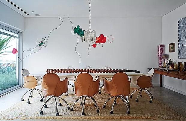 Sala de jantar | Poltronas giratórias Incisa, de  Vico Magistretti para De Padova, distribuem-se  em torno da mesa Clipper, de Carlo Colombo  para Poliform, tudo na Casual Interiores,  sobre um tapete aubusson. A pintura na parede  é de Chiara Banfi, na G (Foto: Victor Affaro e Carlos Andres Varela)