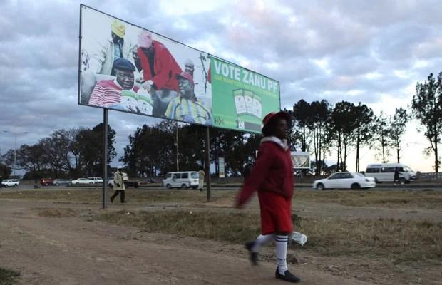 Criança passa por placa que promove o presidente do Zimbábue, Robert Mugabe (Foto: Philimon Bulawayo/Reuters)