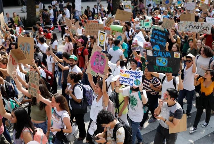 Manifestantes empunham cartazes em protesto pelo clima na Cidade do México nesta sexta (20). — Foto: Carlos Jasso/Reuters