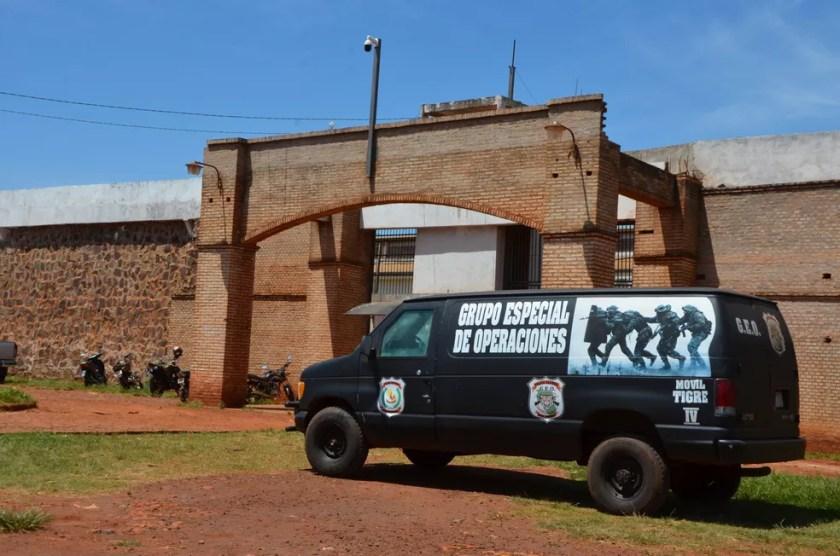 Uma van da polícia paraguaia é vista na entrada da Penitenciária Regional de Pedro Juan Caballero, no Paraguai, neste domingo (19) — Foto: Marciano Candia/AP