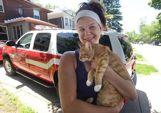 Tara Dennis posa com o gato após ambos serem resgatados de árvore em Erie, na Pensilvânia (EUA) (Foto: Erie Times-News, Jack Hanrahan/AP)