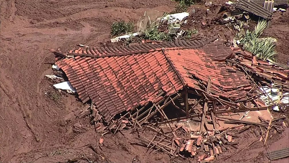 Casa fica abaixo da lama após rompimento de barragem — Foto: TV Globo