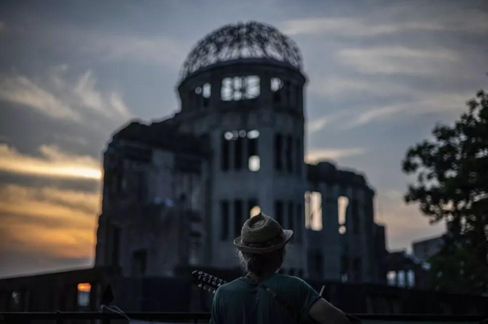 Homem toca violão em frente a um antigo prédio de governo de Hiroshima, hoje conhecido como a Cúpula da Bomba Atômica — Foto: Philip Fong / AFP