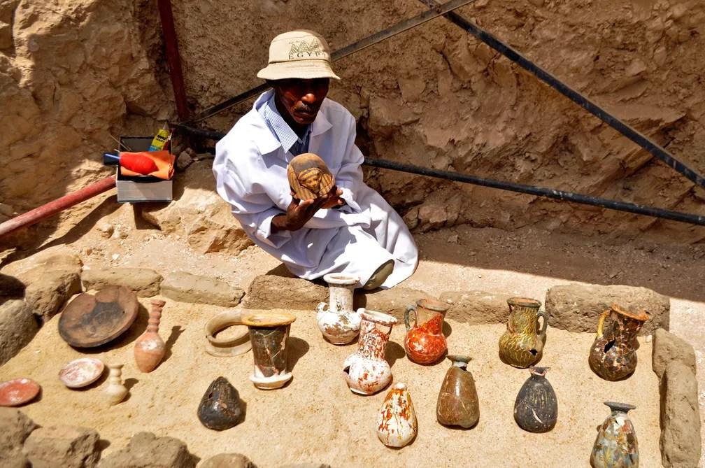 Homem mostra artefato descoberto em tumba de 3,5 mil anos no Egito  (Foto: Stringer/AFP)