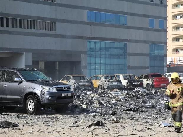Bombeiro caminha entre carros atingidos por destroços de prédio em chamas em Sharjah, nos Emirados Árabes Unidos, na quinta (1º) (Foto: AP Photo)