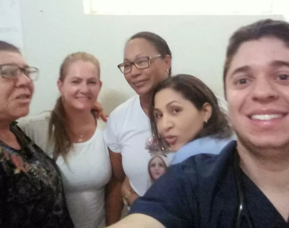 Na foto, Bila aparece com a enfermeira Mara e outros colegas de trabalho — Foto: Arquivo pessoal