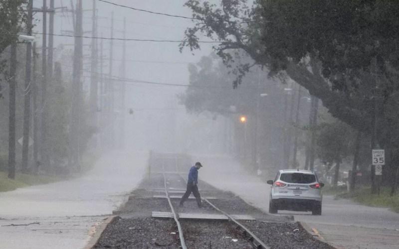 Homem é visto caminhando em meio às chuvas provocadas pelo furacão Delta em Lake Charles, na Louisiana, na sexta-feira (9) — Foto: ReutersAdrees Latif